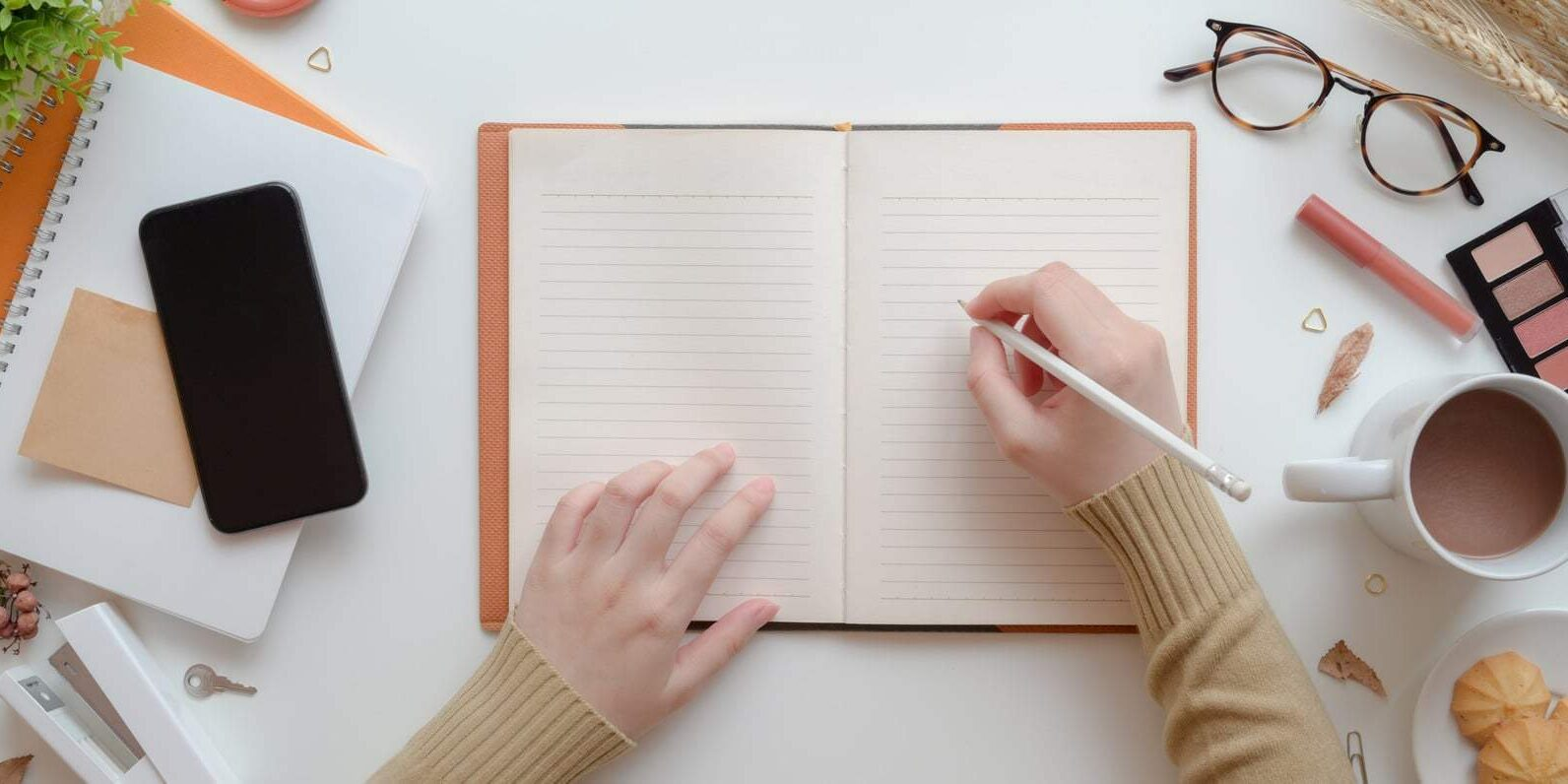 Top view of young female writing on blank notebook in warm beige feminine workspace concept with make up and office supplies